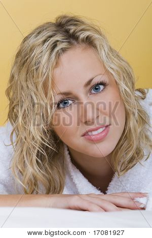 Studio shot of a beautiful young woman with bright blue eyes wearing a bath robe laying down and relaxing.