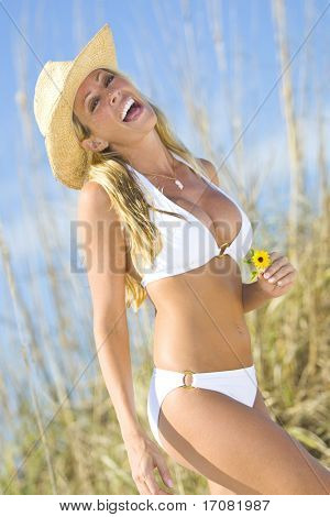 A beautiful blond haired blue eyed model wearing a white bikini laughs while holding a flower amid tall grass