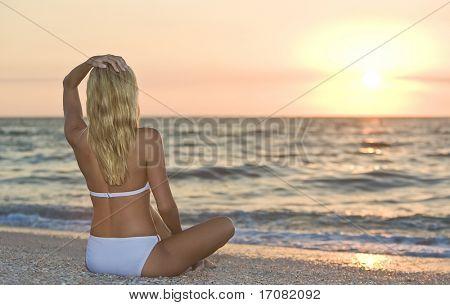 A beautiful young blond woman in a white bikini sits cross legged on a beach at sunset