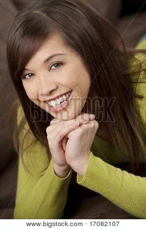 A beautiful young oriental woman with a wonderful toothy smile laying down and relaxing on her settee