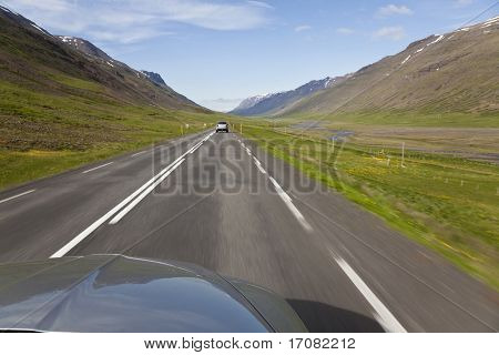 A slow shutter speed point of view shot driving through the highlands of Iceland.The focus is on the bonnet of the car and the motion blur conveys speed.