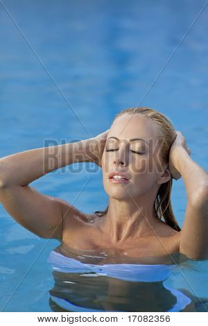A beautiful and sexy young blond woman wearing a white bikini pushes her hair back as she emerges from a turquoise blue swimming pool. Spa, healthy living and health club concept.