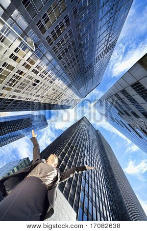 High Dynamic Range HDR photograph if a businesswoman arms raised surrounded by modern city high rise skyscraper office buildings