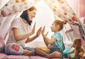 Happy loving family. Mother and her daughter girl play in children room. Funny mom and lovely child  poster