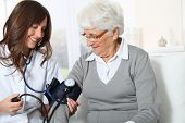 foto of 70-year-old  - Closeup of nurse checking senior woman blood pressure - JPG