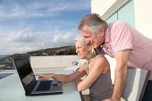 stock photo of old couple  - Senior couple sitting outside with laptop computer - JPG