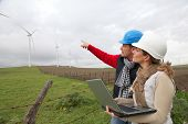 stock photo of turbines  - Engineers working by wind turbines field - JPG