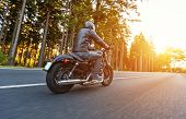 Back view of motorcycle driver driving in beautiful sunset poster