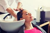 beauty and people concept - happy young woman with hairdresser washing head at hair salon poster