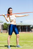 Постер, плакат: Portrait of female athlete about to throw a javelin in the stadium