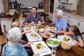 Multi-generation family talking while having meal in kitchen at home poster