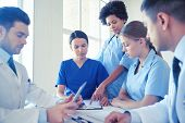 hospital, medical education, health care, people and medicine concept - group of doctors with tablet poster