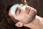 Man having cosmetic mask in spa salon poster