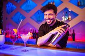 Portrait of bartender smiling while holding cocktail shaker at illuminated bar counter poster