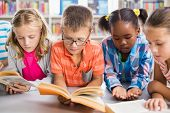 Kids reading a book in library at school poster