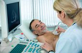image of ultrasound machine  - Doctor is using ultrasound machine to scan the heart of a senior male patient - JPG