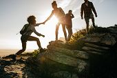 Young People On Mountain Hike At Sunset poster
