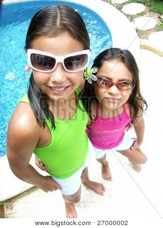 Hispanic girl with sunglasses enjoying a swimming pool.