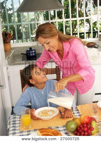 Madre hispana verter leche y cereales de maíz a su hija.