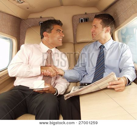 Business man shaking hands and working at private jet.