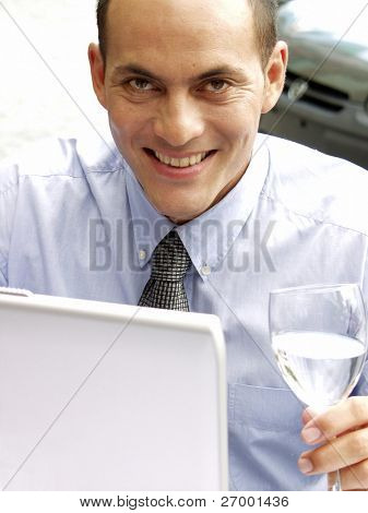 Young business man working with a laptop while drinking water.