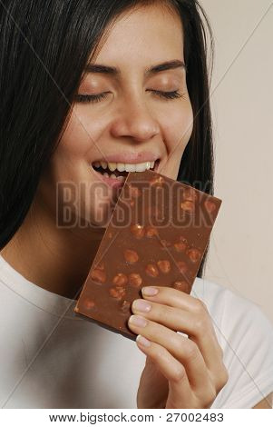 Young woman eating a nuts chocolate.