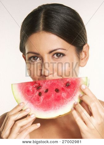 Young woman holding a fresh water melon. Young woman eating a fresh water melon.