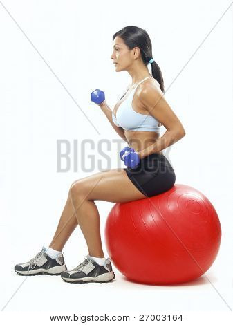 Young Woman doing fitness exercise with a red ball.