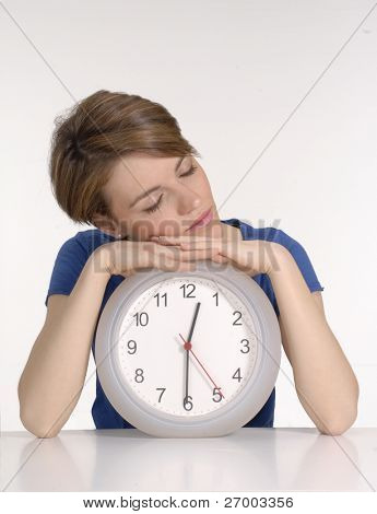 Young woman sleeping over a clock on white background.