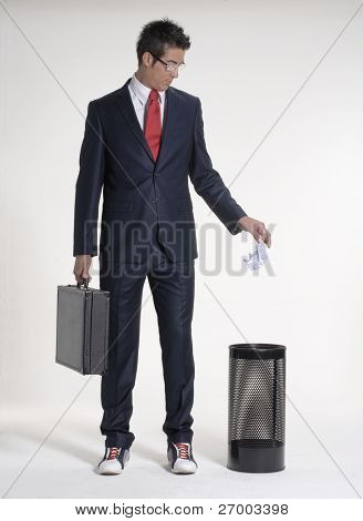 Young businessman dropping a paper in a waste basket. Young businessman dropping a paper in a trash bin.