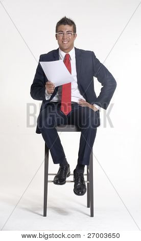 Young businessman sitting on a chair and holding a document on white background.