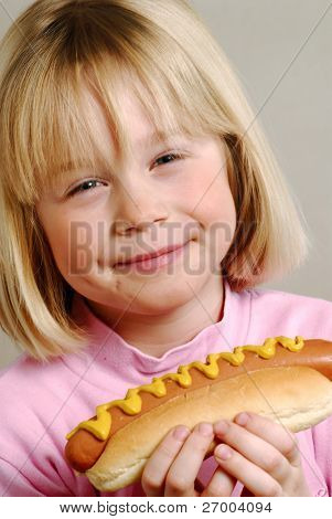 Little girl eating hot dog,Kid eating hot dog.