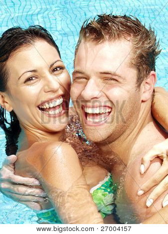 Hispanic young couple enjoying in a swimming pool.