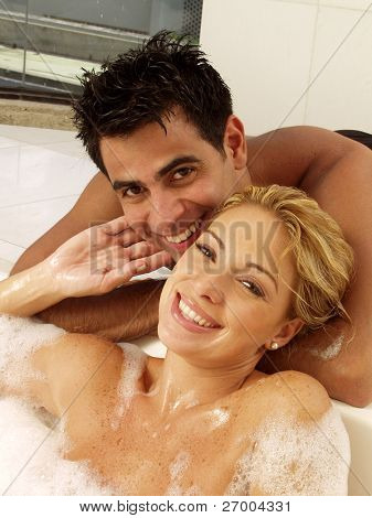Young couple enjoying together in a jacuzzi. Young woman applying shampoo to a man.