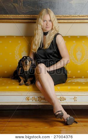 Young blonde woman with a little dog sitting on an elegant yellow sofa.