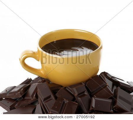 Yellow cup over a chocolate sticks on white background.