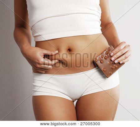 Young woman body detail holding a chocolate bar.