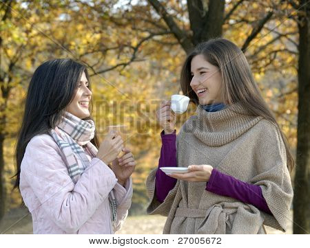 Outdoors autumn young women enjoying and drinking hot coffe. Outdoors autumn young latin women enjoying and drinking hot drinks.