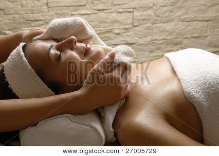 Bella joven recibiendo un tratamiento de cara en el salón de belleza.