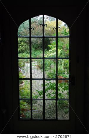 Silhouette Of A Gothic Window Overlooking A Lush Garden