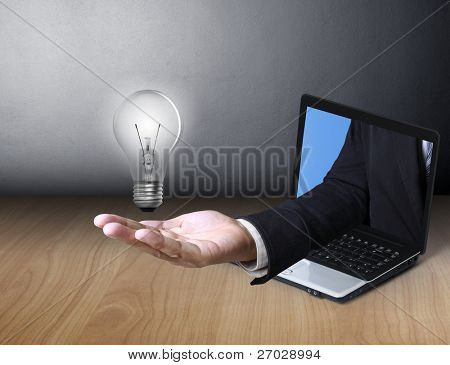 Light bulb in hand and a laptop