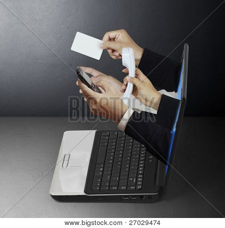hand sticking through a laptop giving a card and a telephone