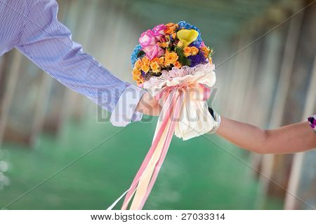 two hand holding beautiful flower bouquet
