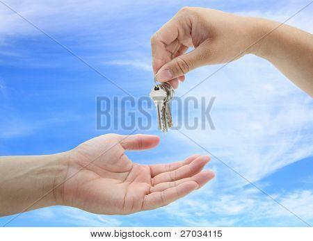 hombre entrega el conjunto de casa claves contra el cielo azul