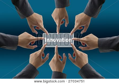 A diverse business team with hands together push Innovation button