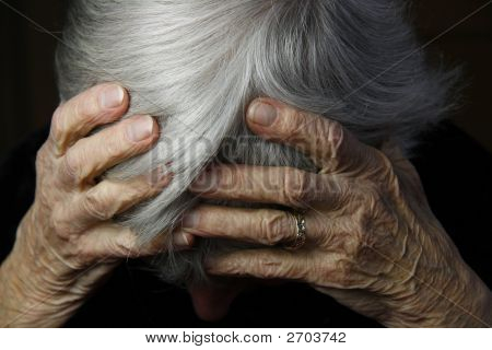 Wrinkled Hands Covering Head While Crying