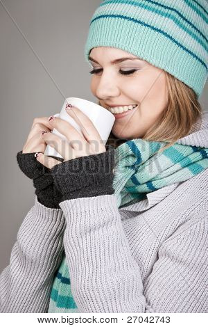 Pretty winter teenage girl holding mug with hot beverage