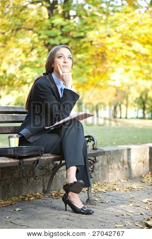 young thinking businesswoman sitting on bench in park