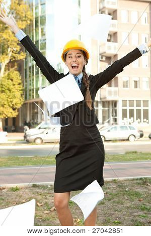 happiness female engineer celebrating her success, throwing paper in the air
