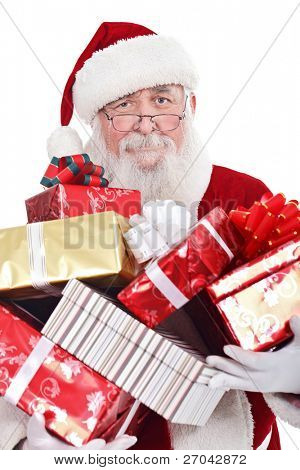 Santa Claus or Father Christmas holding a large pile of presents, isolated on white background.